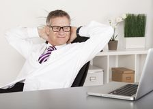 Relaxed Physician Smiling While Watching at Laptop Stock Photo