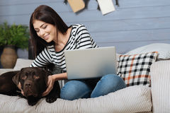 Relaxed pleased woman enjoying leisure time with her pet Stock Image