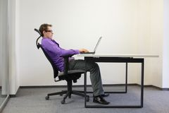 Relaxed position at laptop. Business man on chair in his office Royalty Free Stock Images