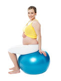 Relaxed pregnant woman sitting on pilate ball Royalty Free Stock Image