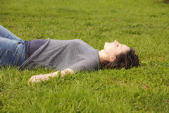 Relaxed pregnant woman. Relaxed young pregnant woman on the grass in park eyes closed royalty free stock images