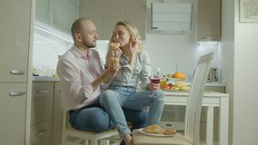 Passionate couple enjoying lunch in domestic kitchen. Relaxed pretty adult woman with glass of red wine sitting on boyfriend`s lap sharing croissant while stock video