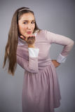 Relaxed pretty model with pink dress on kissing at camera Royalty Free Stock Image