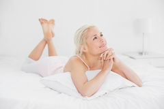 Relaxed pretty woman with joined hands in bed Stock Photos