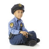 Relaxed but Ready. A handsome elementary policeman happily sitting crossed legged, his gun held near his lap.  On a white background Royalty Free Stock Photos