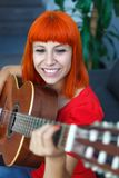 Relaxed redhaid woman playing guitar Royalty Free Stock Photo