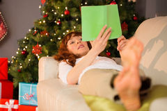 Relaxed redhead reading on the couch at christmas Royalty Free Stock Photography