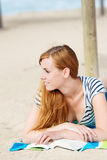 Relaxed Redhead Woman Reading Book On Beach Royalty Free Stock Photo