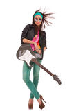 Relaxed rock and roll babe with windy hair. Leaning against her electric guitar on white background stock image
