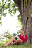 Relaxed 20s girl reading a summer book under a tree. Outdoors reading - beautiful young suntanned blond woman reading a book in the shade of a tree for freshness Stock Photography