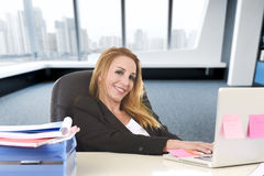 Relaxed 40s woman with blond hair smiling confident sitting on office chair working at laptop computer Royalty Free Stock Photography