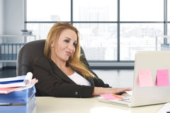 Relaxed 40s woman with blond hair smiling confident sitting on office chair working at laptop computer. Happy and relaxed 40s woman with blond hair smiling Stock Photo