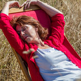 Relaxed 50s woman enjoying sun warmth on her deckchair. Sun warmth wellbeing - sleeping mature woman enjoying sunbathing on deckchair,closing eyes in summer stock photography