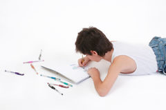 Relaxed schoolboy drawing. European schoolboy drawing with colour pens on the floor Royalty Free Stock Photo