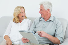 Relaxed senior couple using digital tablet at home Stock Images