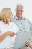 Relaxed senior couple using digital tablet at house Royalty Free Stock Photography