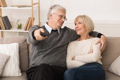 Relaxed senior couple watching television at home stock images