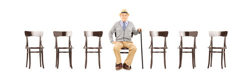 Relaxed senior gentleman sitting on a wooden chair Stock Image