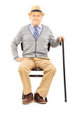 Relaxed senior man sitting on a wooden chair and looking at came Royalty Free Stock Image
