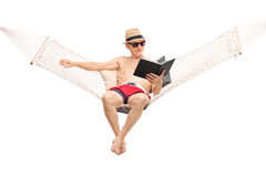 Relaxed senior sitting in a hammock and reading book Stock Photos