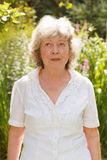Relaxed senior woman in garden Royalty Free Stock Image