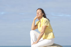 Relaxed senior woman ocean background Stock Images