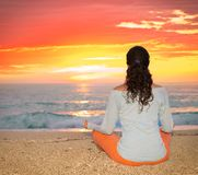 Brunette woman sitting on a tropical beach at sunset. Greece. royalty free stock photos