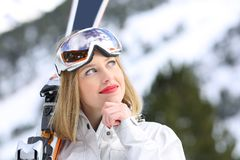 Relaxed skier thinking looking at side in winter. Relaxed skier thinking looking at side holding skis in winter holiday stock photos