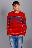 Relaxed smile. Man in striped red sweater standing isolated on grey background and limply smiling Royalty Free Stock Photo