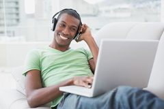 Relaxed smiling Afro man with headphones using laptop on sofa Royalty Free Stock Photography