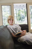 Relaxed Smiling Boy With Book On Sofa. Portrait of a relaxed smiling boy sitting on sofa with book in living room Stock Image