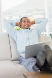 Relaxed smiling businessman on the couch with laptop Stock Photo