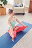 Relaxed smiling girl doing lotus posture on yoga mat Stock Image