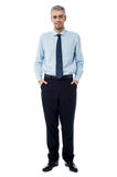 Relaxed smiling middle age business man. Confident businessman with hands in pockets Royalty Free Stock Photo