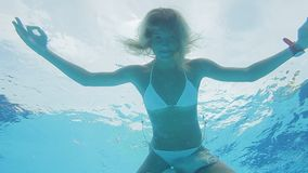 Relaxed smiling woman in bikini flying in a swimming pool in lotus position. Underwater yoga. Relaxed smiling woman in bikini flying in a swimming pool in lotus stock footage
