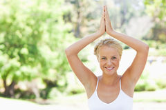 Relaxed smiling woman doing yoga in the park Stock Images