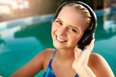 Relaxed smiling woman listening to music in headphones bathing in swimming pool. Blonde girl enjoys favourite song with royalty free stock photos
