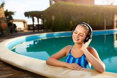 Relaxed smiling woman listening to music in headphones bathing in swimming pool. Blonde girl enjoys favourite song with royalty free stock image