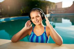Relaxed smiling woman listening to music in headphones bathing in swimming pool. Blonde girl enjoys favourite song with royalty free stock photo