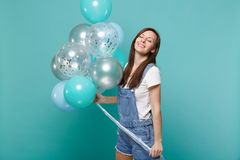Relaxed smiling young woman in denim clothes keeping eyes closed celebrating, holding colorful air balloons isolated on. Blue turquoise wall background royalty free stock image