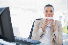 Relaxed sophisticated businesswoman smelling coffee. In bright office royalty free stock photo