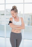 Relaxed sporty blonde wearing armband holding mp3 player Stock Photography
