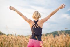 Relaxed sporty woman, arms rised, enjoying nature in the beautifull morning at wheet field. stock image