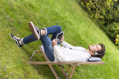 Relaxed student listening to music with closed eyes in garden Royalty Free Stock Images