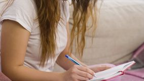 Relaxed studying casual girl sitting home writing. Relaxed studying style. home education. casual teenage girl sitting on a sofa writing in her notebook Royalty Free Stock Photo