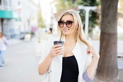 Relaxed stylish woman drinking coffee outside on urban background Royalty Free Stock Photography