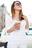 Relaxed stylish businesswoman looking away, outside on urban background Stock Photo