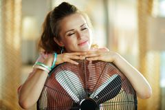 Relaxed stylish woman embracing metallic floor standing fan stock image