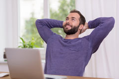Relaxed successful bearded man. Sitting at his desk with his hands clasped behind his head staring up into the air with a smile of pleasure Stock Photos