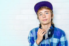 Relaxed teen boy. Modern teenage boy enjoys the music in headphones. Studio shot. Youth culture Royalty Free Stock Images
